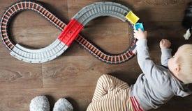 Een kleine jongen speelt een spoorweg van kinderen Het mamma let hierboven op haar zoon van Het kind wordt gefascineerd door de t royalty-vrije stock foto's