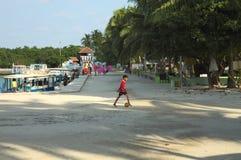 Een kleine jongen speelt voetbal in de haven stock fotografie