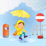 Een kleine jongen springt in een regenwatervulklei om pret te maken Stock Afbeelding