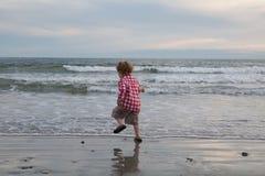 Een kleine jongen springt en danst door de oceaan stock foto's