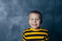 Een kleine jongen stelt voor een grijs-blauwe concrete muur Portret van een glimlachend kind gekleed in zwarte en gele gestreept stock afbeelding