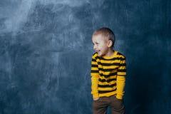 Een kleine jongen stelt voor een grijs-blauwe concrete muur Portret van een glimlachend kind gekleed in zwarte en gele gestreept stock fotografie