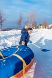 Een kleine jongen van 3 jaar oud, in de winter op straat sleept buizenstelsel, voor het berijden van een heuvel, in de handen van royalty-vrije stock fotografie