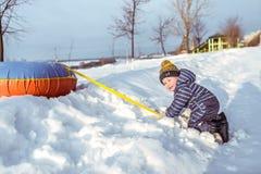 Een kleine jongen van 3 jaar oude spelen op een heuvel in de winter, sneeuwafwijkingen en bomen Vakantie in de de wintervakantie  stock fotografie