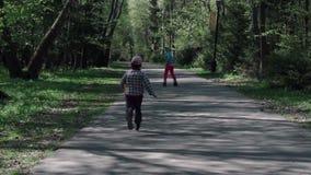 Een kleine jongen vangt het meisje dat op rolschaatsen berijdt Langzaam-Mo stock videobeelden