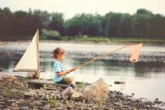 Een kleine jongen vist op het meer in sammer royalty-vrije stock afbeelding