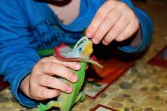 Een kleine jongen voedt een stuk speelgoed dinosaurus Een kind speelt met zijn stuk speelgoed dinosaurus royalty-vrije stock afbeeldingen