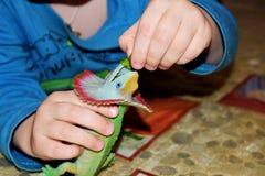 Een kleine jongen voedt een stuk speelgoed dinosaurus Een kind speelt met zijn stuk speelgoed dinosaurus royalty-vrije stock fotografie