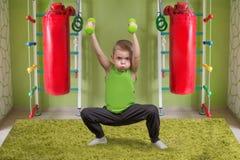 Een kleine jongen voert een oefening met domoren uit De kindhurkzit met domoren Sport, gezonde levensstijl Royalty-vrije Stock Foto