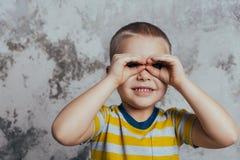 Een kleine jongen vouwde zijn wapens door de ogen die voor een grijze concrete muur stellen Portret van een glimlachend kind die  stock afbeelding