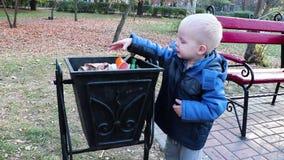 Een kleine jongen werpt huisvuil in het afval in de straat Het concept afvalbeheer en milieubescherming Juist paren stock video