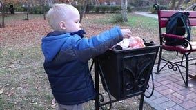 Een kleine jongen werpt huisvuil in het afval in de straat Het concept afvalbeheer en milieubescherming Juist paren stock footage