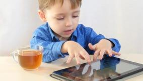 Een kleine jongen zit bij een lijst en speelt op een tablet het kind drinkt thee - 2 Royalty-vrije Stock Afbeeldingen