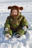 Een kleine jongen zit in de sneeuw Stock Afbeelding