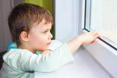 Een kleine jongen zit door het venster en onderzoekt de afstand Royalty-vrije Stock Afbeeldingen