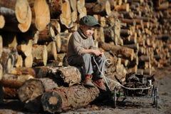 Een kleine jongen zit op a op een houten bal stock afbeeldingen