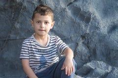 Een kleine jongen zit op een rots Stock Foto