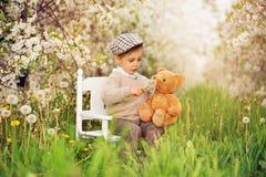Een kleine jongensescapist zit op witte lijst met een teddybeer in een bloeiende kersenboomgaard stock afbeelding