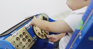 Een kleine jongensspelen in een houten onderwijsmachine Montessoristuk speelgoed stock video