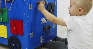 Een kleine jongensspelen met een Montessori busybord Ontwikkelingsmachine Houten stuk speelgoed stock footage