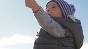 Een kleine kindspelen met speelgoed op de overzeese kust in de winterkleren en een hoed stock video