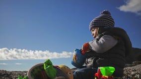 Een kleine kindspelen met speelgoed op de overzeese kust in de winterkleren en een hoed stock videobeelden