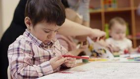 Een kleine kindzitting bij de lijst, holding een rode teller, beslist wat, op de achtergrond, kinderen te trekken schildert op stock footage