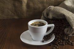 Een kleine kop van hete koffie op een lijst met koffiebonen Royalty-vrije Stock Foto