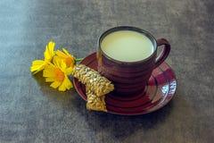 Een kleine kop van melk, broodstokken en helder boeket van gele D Stock Foto