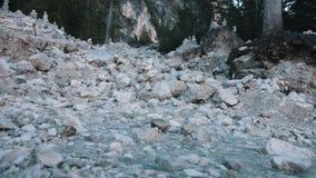 Een kleine kreekstromen door de rotsen stock videobeelden