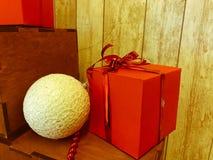 Een kleine leuke witte Kerstboomdecoratie, een bal en van het Nieuwjaar feestelijke decoratie en een rode giftdoos stock afbeelding