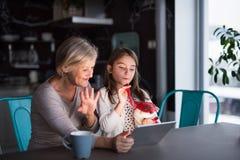Een kleine meisje en een grootmoeder met tablet thuis royalty-vrije stock fotografie