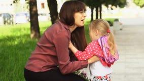 Een kleine meisjeslooppas aan haar moederzitting op een bank stock video