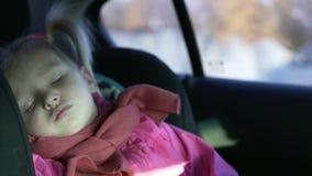 Een kleine meisjesritten in een auto in een autozetel stock video