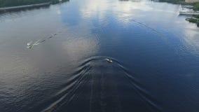Een kleine motorboot glijdt zeer snel over de oppervlakte van de rivier Het spoor van de waterrimpeling uit van de boot De camera stock video