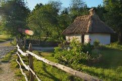 Een kleine Oekraïense die hut met een strodak door een houten omheining wordt omringd royalty-vrije stock foto