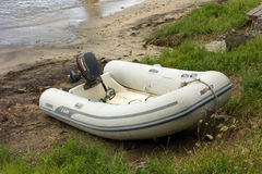 Een kleine opblaasbare rubberboot op een strand Stock Afbeeldingen