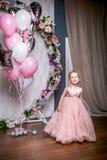 Een kleine prinses in een mooie roze kleding bevindt zich naast ballons en een bloemboog, houdend een kleding met haar handen en  royalty-vrije stock foto
