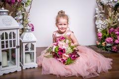 Een kleine prinses in een mooie roze kleding zit op de vloer dichtbij bloemtribunes en de lantaarns, houdt een boeket van pioenen stock fotografie
