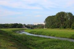 Een kleine rivier stroomt tussen de banken aan de bruggen royalty-vrije stock foto's