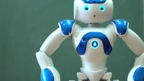 Een kleine robot met een menselijk gezicht en een humanoidlichaam