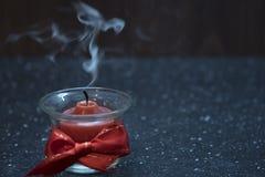 Een kleine rode kaarsbrandwonden in een glaskom met een rood lint stock foto