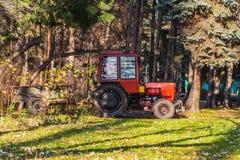 Een kleine rode tractor met aanhangwagen is onder groene en gele bomen stock fotografie