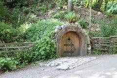 Een kleine rond gemaakte oude het kijken houten deur royalty-vrije stock afbeeldingen