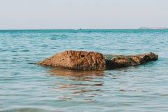 Een kleine rots in het gestemde overzees, stock afbeelding