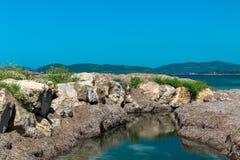 Een kleine stroom met rotsachtige banken stroomt in de Middellandse Zee stock afbeeldingen