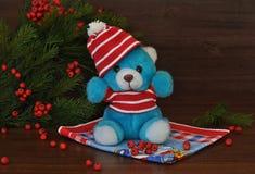 Een kleine stuk speelgoed teddybeer in een rode hoed en nette takken met rode bessen naast het op een oude houten achtergrond Stock Fotografie