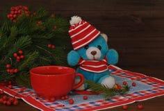 Een kleine stuk speelgoed teddybeer in een rode hoed, nette takken met rode bessen en rode kop naast het op een oude houten achte Stock Afbeeldingen