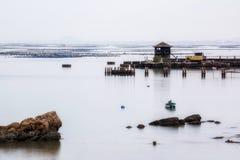 Een kleine toren bij de visserij van pijler met vlotte blauwe overzees en bezinning van hemel zoals spiegel, lang blootstellingss Royalty-vrije Stock Afbeelding