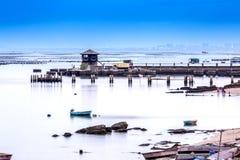 Een kleine toren bij de visserij van pijler met vlotte blauwe overzees en bezinning van hemel zoals spiegel, lang blootstellingss Royalty-vrije Stock Afbeeldingen